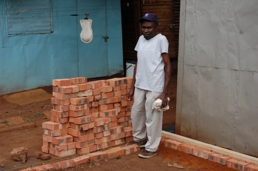 Claudios with a stack of bricks for his new home's foundation.